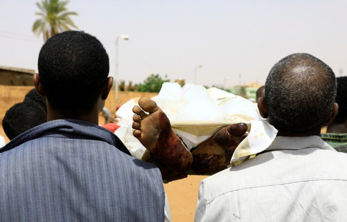 Locals and relatives of three Sudanese men riddled with bullets carry one of the three corpses in the city of Omdurman across the River Nile from Khartoum