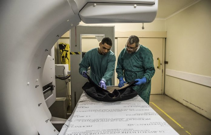 Gang evidence: Professor Johan Dempers and forensic pathology officer Almarco Marcus inspect bullet holes in a jacket.