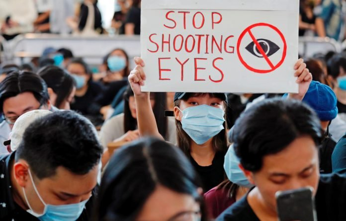 Anti-extradition bill protesters attend a mass demonstration after a woman was shot in the eye during a protest at Hong Kong International Airport.