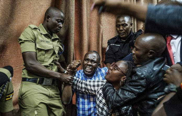 Baring it all: Supporters of Ugandan human rights activist Stella Nyanzi are roughed up by police at court.