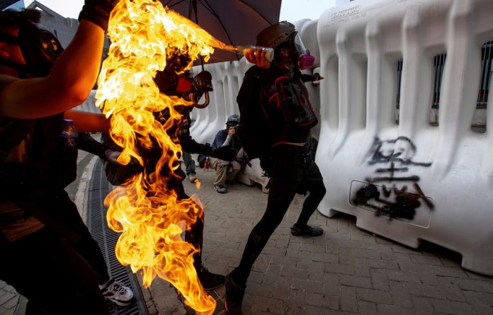 An anti-government protester throws a molotov cocktail during a demonstration near the Legislative Council building in Hong Kong