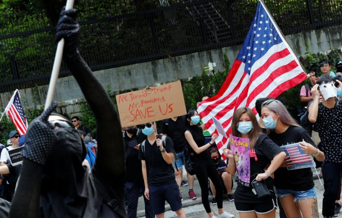 People hold signs and attend a rally to the US Consulate General in Hong Kong.