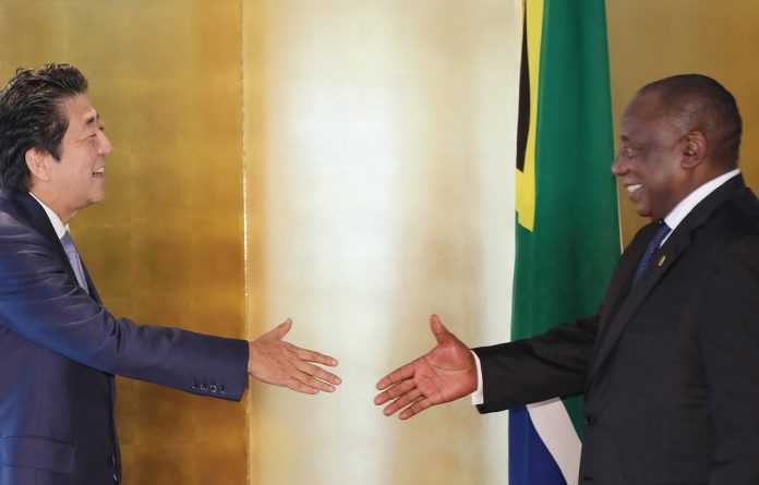Japanese Prime Minister Abe and South African President Cyril Ramaphosa greet each other at the TICAD 7 conference
