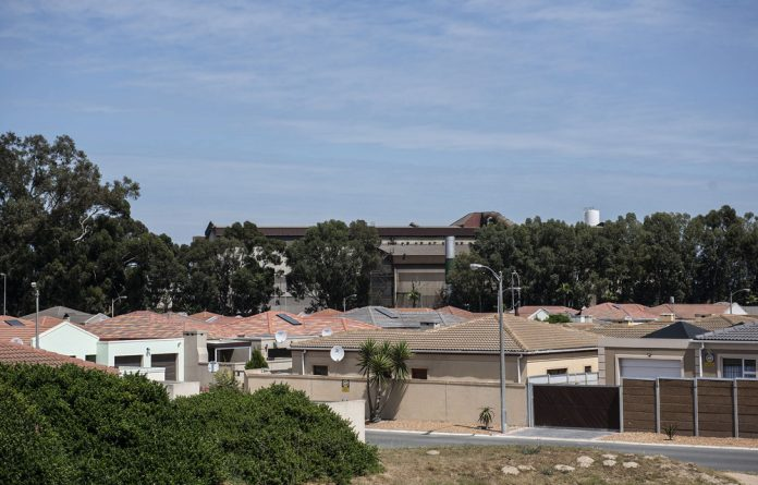 Dirty backdrop: The Cisco factory can be seen behind this housing estate in Kuils River.