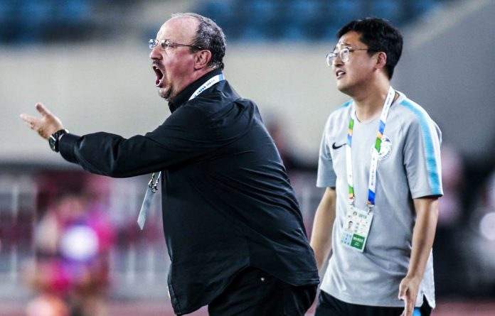 Footballer's wife: Dalian Yifang coach Rafa Benitez is constantly shadowed by his Chinese interpreter.