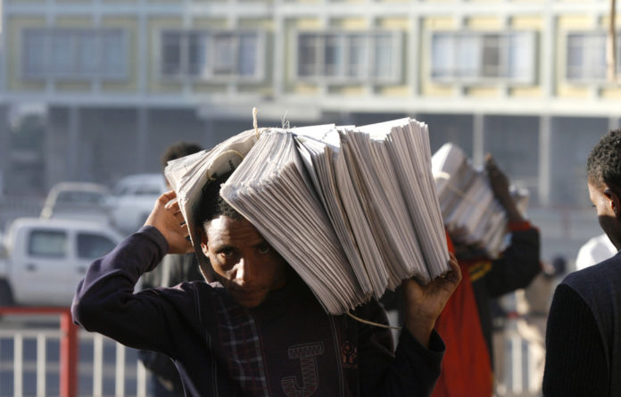 Vendors carry piles of newspapers along a street in Ethiopia's capital Addis Ababa.