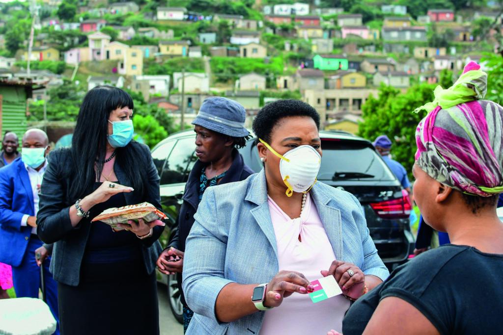 Belinda Scott, Durban's deputy mayor and Nomusa Dube-Ncube, MEC KwaZulu-Natal Economic Development, Tourism and Environmental Affairs hand over sanitisers, masks and sanitary packs in Umlazi township on April 09, 2020 in Durban. (Darren Stewart/Gallo Images)